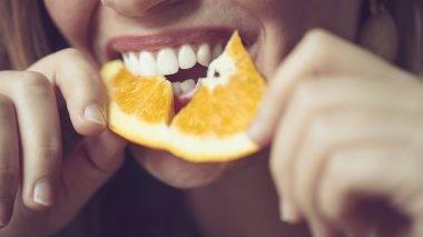 Bilde av en dame som spiser appelsin.